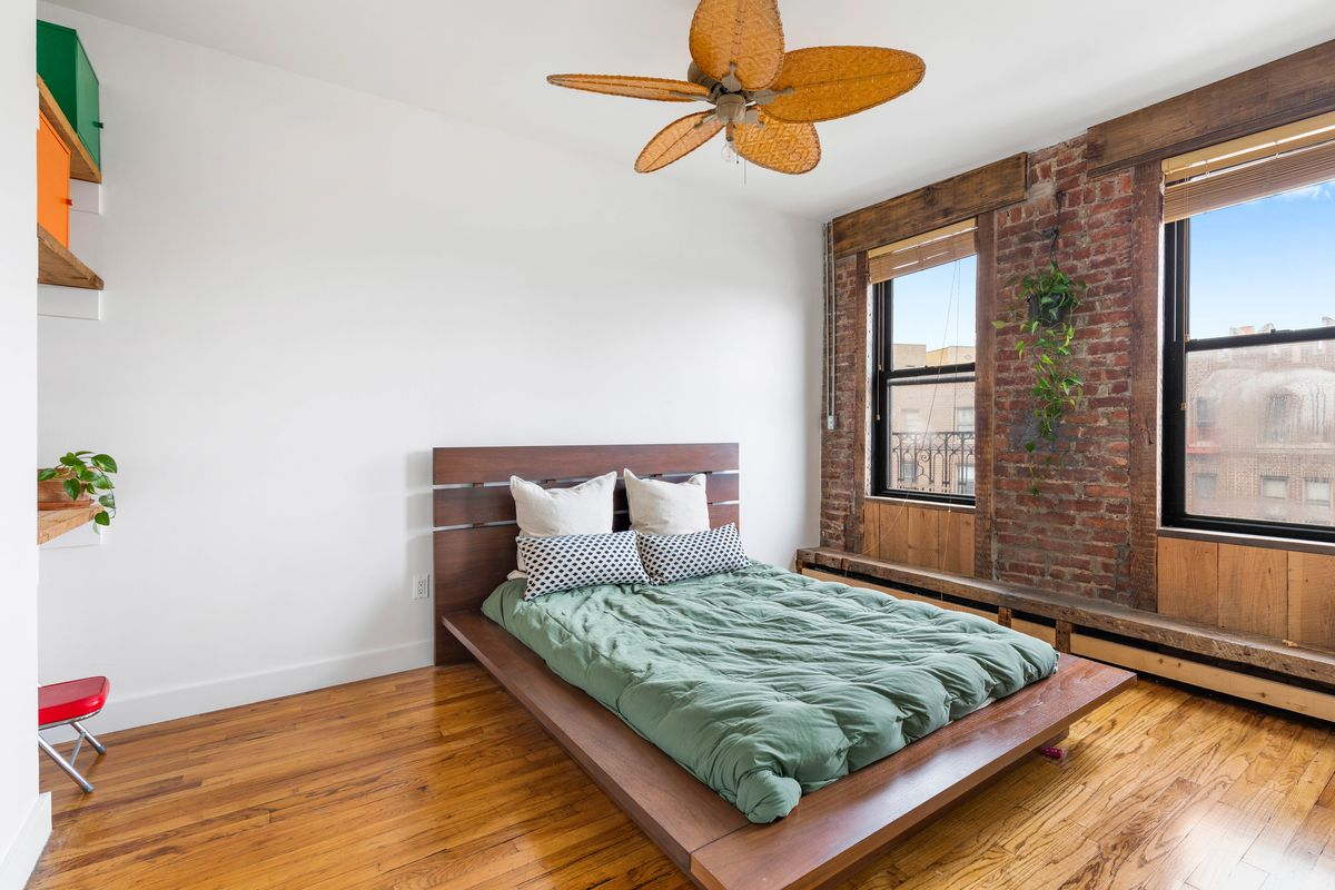A bedroom with a small bed, exposed brick, hardwood floors, two windows, and a ceiling fan with leaf-shaped blades.