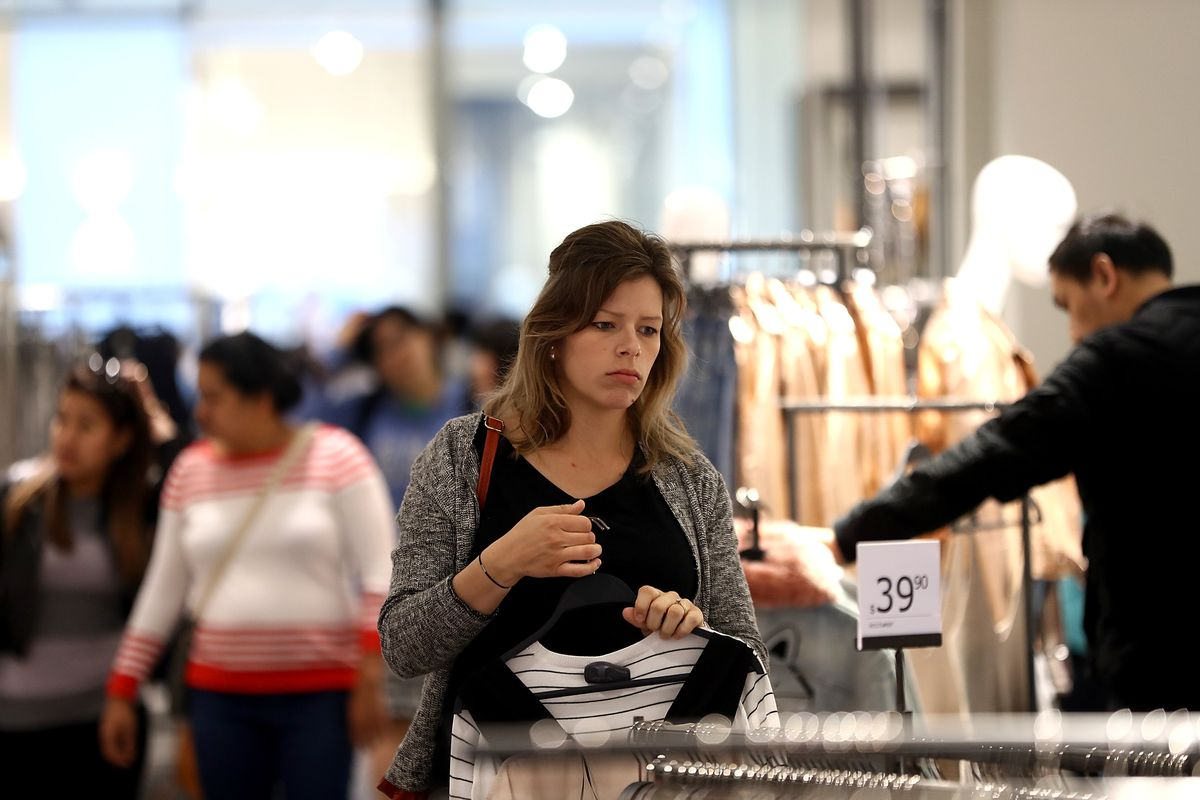 A woman holds a shirt by the hanger, looking at another rack of clothing.
