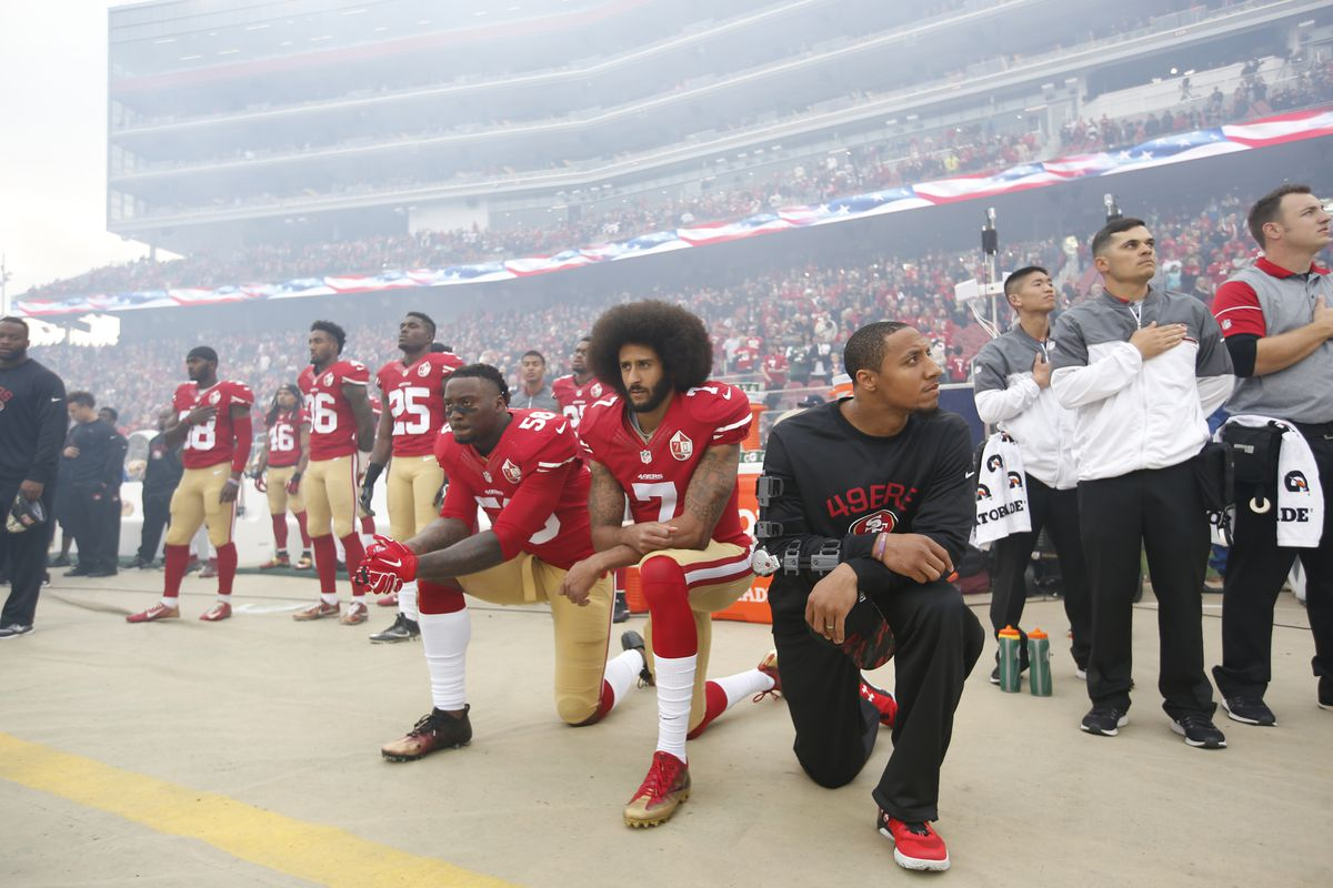 Eli Harold, Colin Kaepernick, and Eric Reid of the San Francisco 49ers kneel during the anthem before playing the New York Jets on December 11, 2016 in Santa Clara, California.
