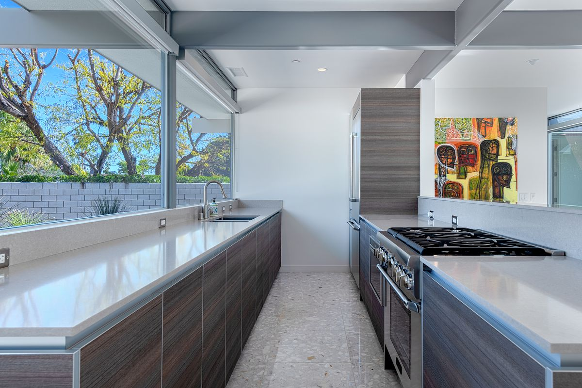 A modern galley kitchen features wood cabinets and large windows that look out onto the backyard.