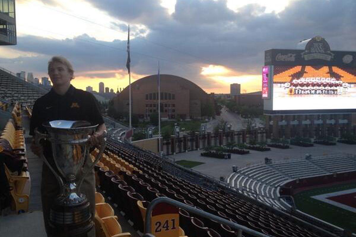 Minnesota goaltender Adam Wilcox, who won 2 awards Tuesday night, posing with the MacNaughton Cup outside TCF Bank Stadium