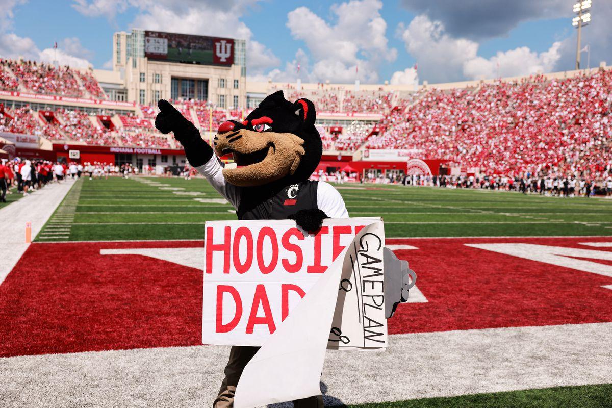 The University of Cincinnati Bearcat mascot holds a sign...