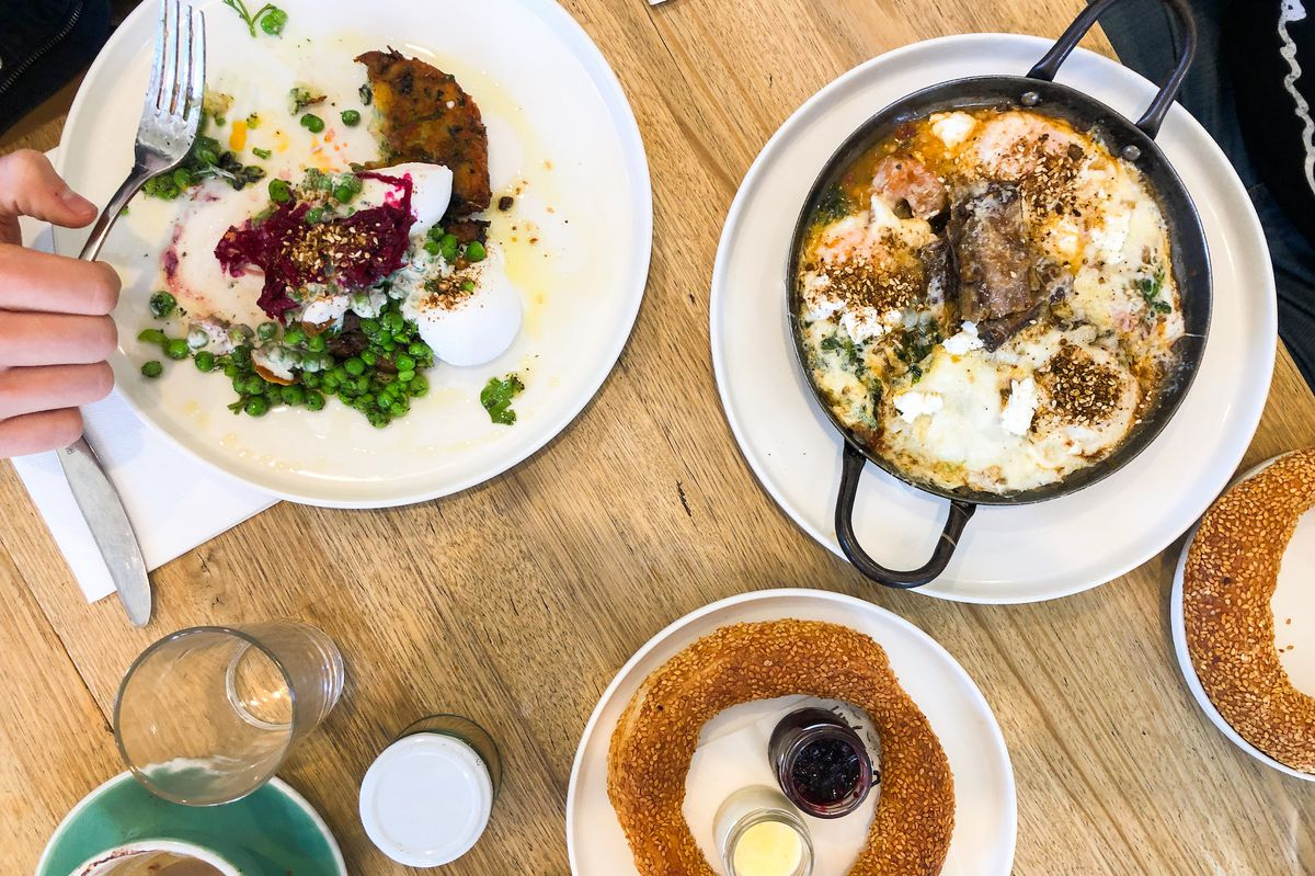 A table shot from above with a baked egg dish, some round seeded rings of bread, and a half eaten plate of eggs and peas