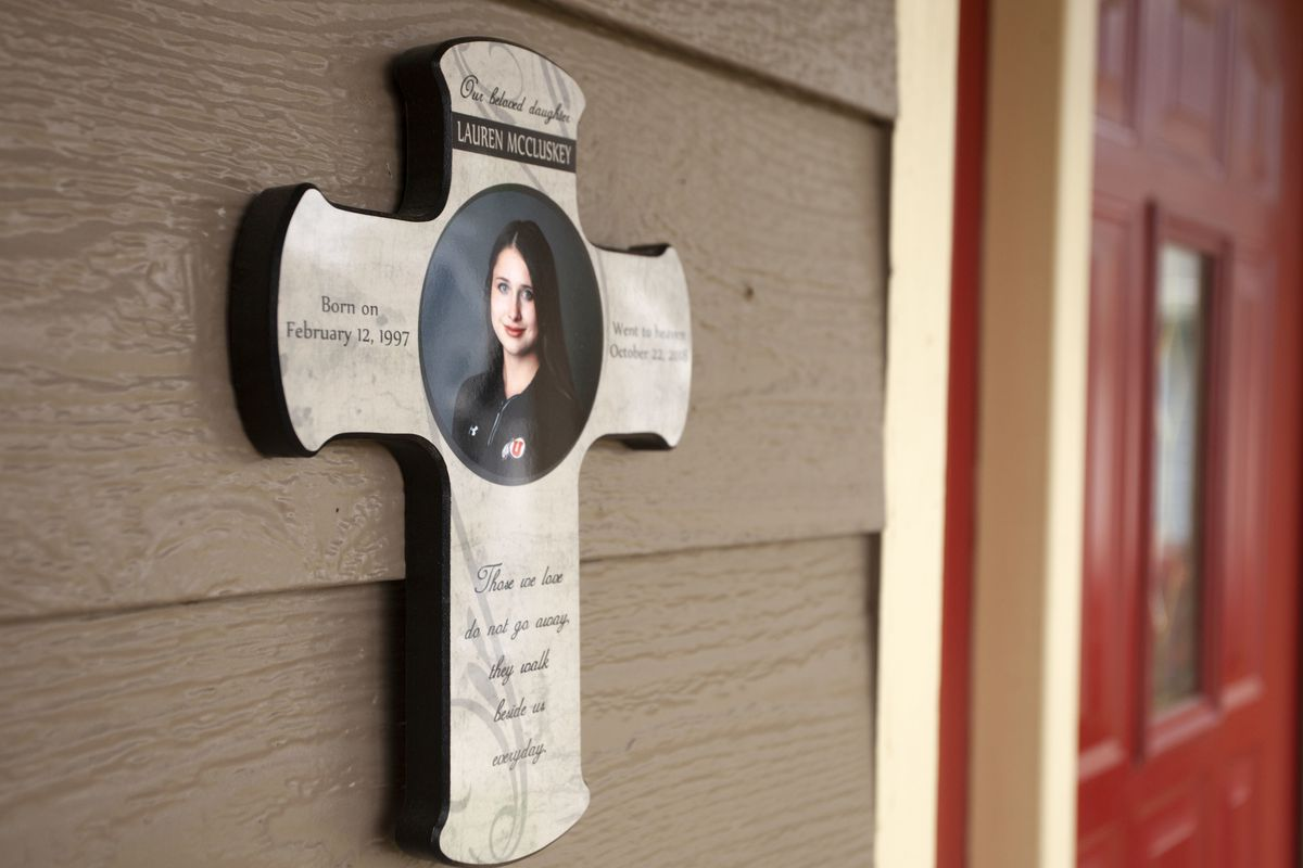 A cross with a photo of Lauren McCluskey hangs outside the McCluskey home on Friday, May 24, 2019, in Pullman, Wash. Lauren McCluskey was murdered in October 2018 on the University of Utah campus.
