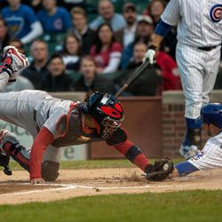 Chicago Cubs' David DeJesus (9) slides past St. Louis Cardinals' catcher Yadier Molina to score in the first inning of a baseball game in Chicago on Tuesday, April 24, 2012.