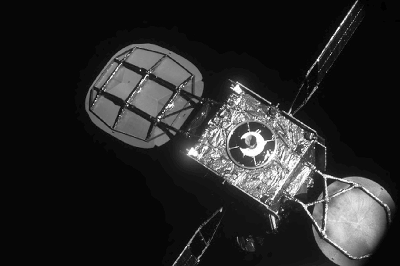 Black and white photo of a satellite above Earth.