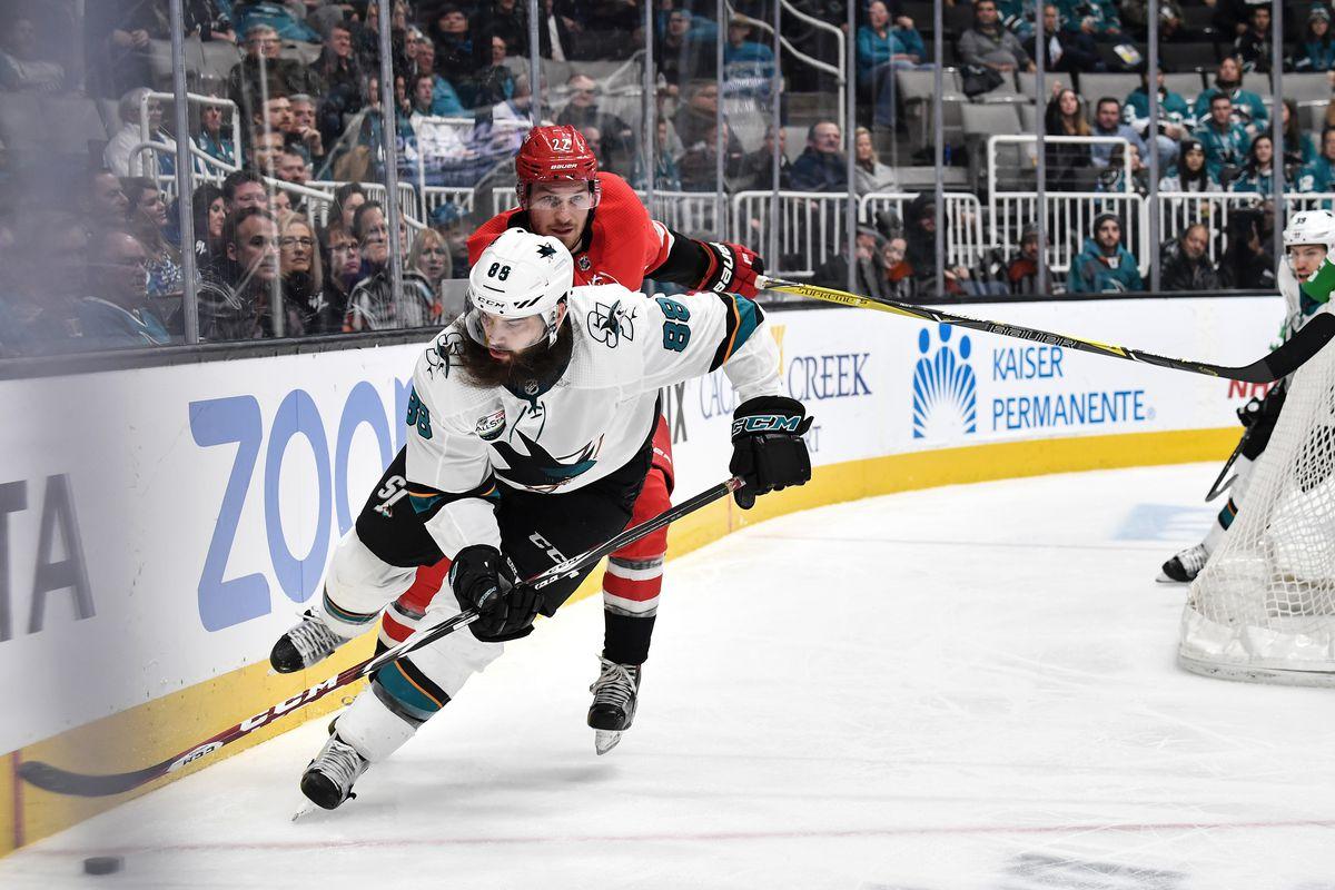 SAN JOSE, CA - DECEMBER 05: Brent Burns #88 of the San Jose Sharks skates with the puck against Brett Pesce #22 of the Carolina Hurricanes at SAP Center on December 5, 2018 in San Jose, California