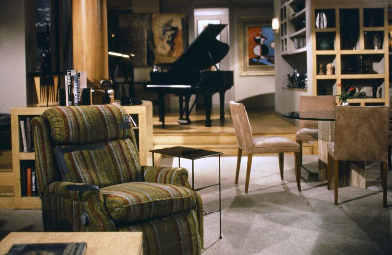 Fraiser Crane's condo has a striped green and brown recliner, black piano, and 90s dining room table.