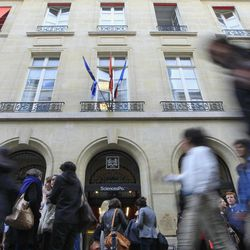Students walk past in front of the entrance of the Institut d'etudes Politiques, or The Paris institute with French and European  flags at half staff above, Wednesday, April 4, 2012.  Richard Descoings, director of the  institute, was found dead in a New York City hotel room, Tuesday afternoon, April 3, 2012.  The Paris institute is better known in France as Sciences Po. It's considered a training ground for France's political, media and administrative elite.