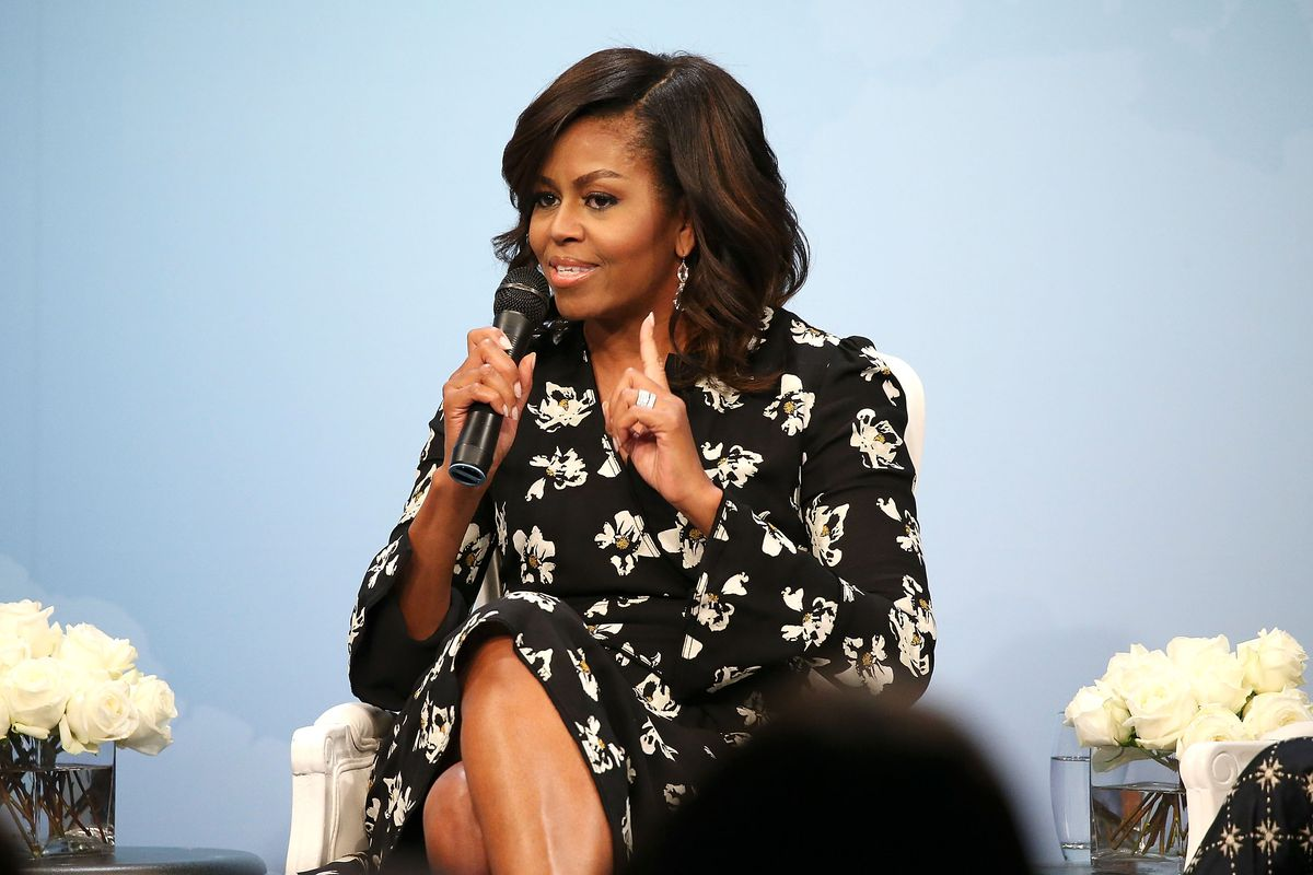 Photo of a woman sitting on a stage holding a microphone.