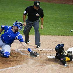 Salt Lake Bees shortstop Rey Navarro (13) slides past Las Vegas 51s catcher Kevin Plawecki (26) during a game at Smith's Ballpark in Salt Lake City on Monday, June 5, 2017.