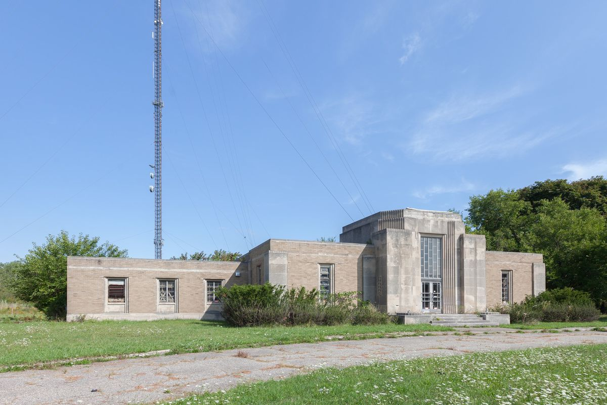 The exterior of the WWJ Building features an Art Deco-style exterior surrounded by grass on a sunny day with a radio tower coming out of the left side near a bushy tree.
