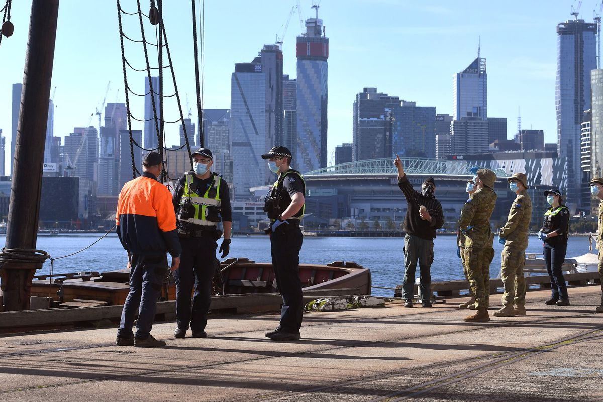 Police in navy and neon yellow speak with a man in a neon orange coat next to a boat, as soldiers in camouflage speak to a man in black who is pointing at the boat's mast. Melbourne's skyscrapers glitter in the winter sun in the background.