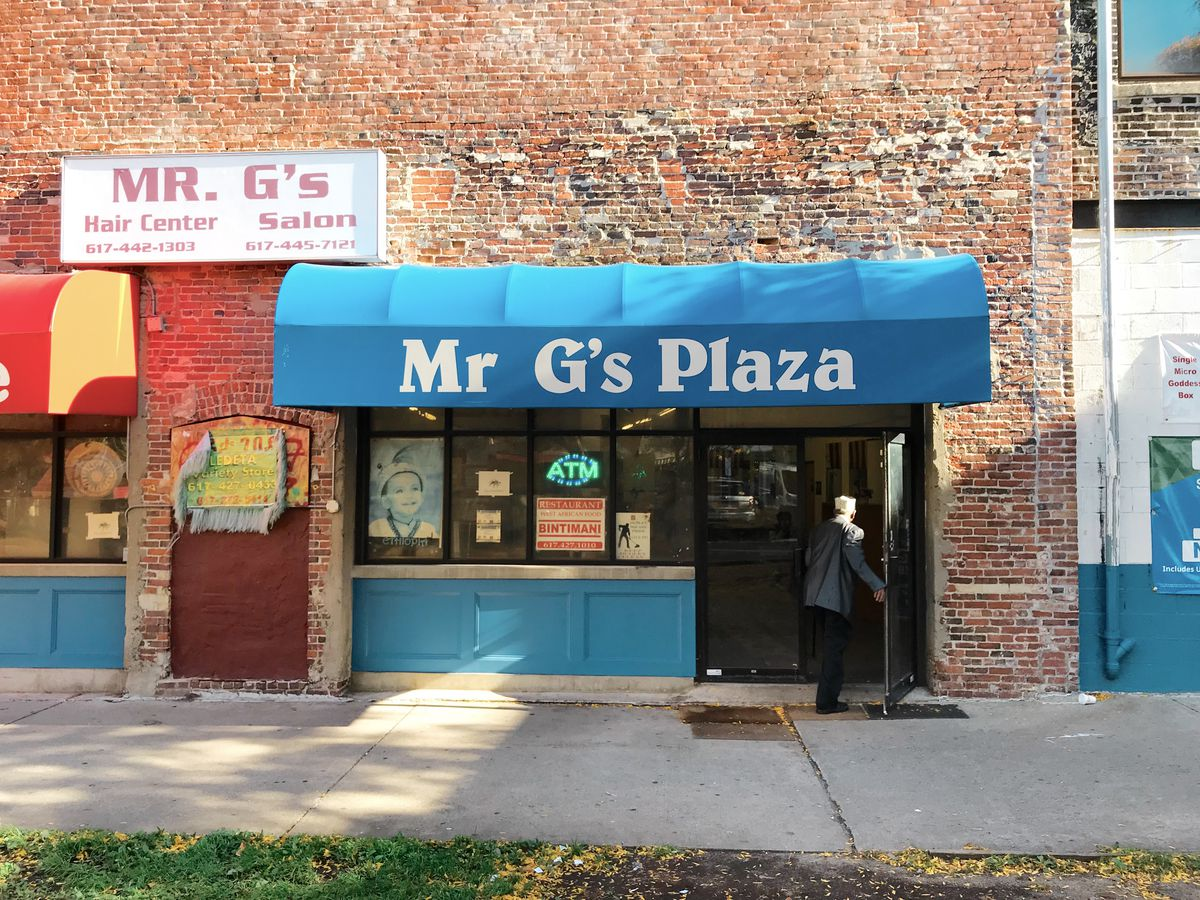 """A brick building with a blue awning that reads """"Mr. G's Plaza"""" in white font."""