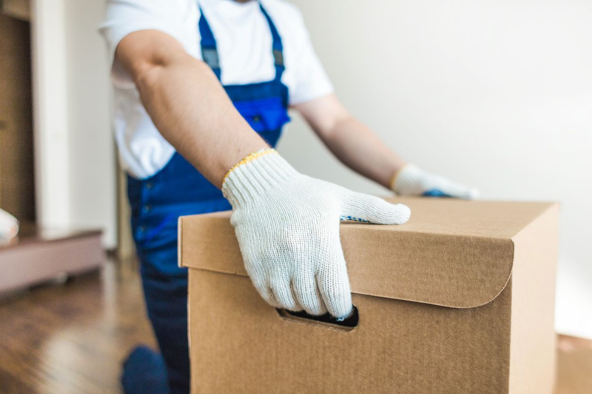 A mover wearing a white t shirt, blue overalls, and white gloves carries out a brown cardboard box from a home.