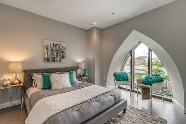 A bedroom with a bed next to a triangular-shaped large window.
