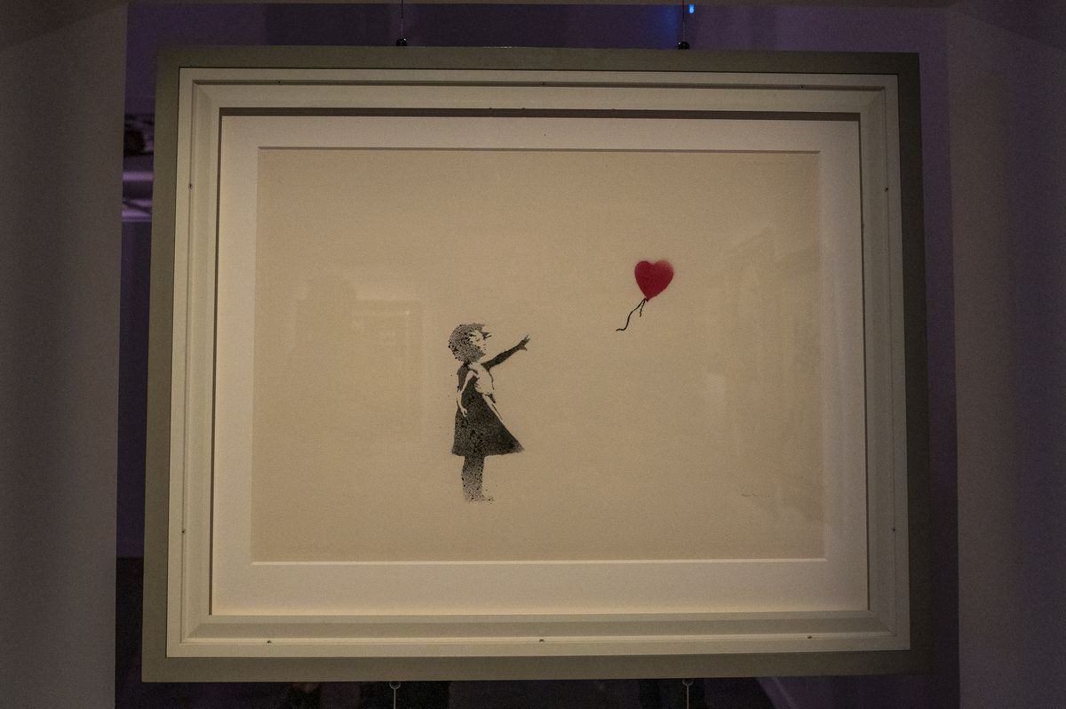 """""""Girl With Balloon"""" is among the 80 works by the mysterious English street artist known as Banksy, in the hugely anticipated exhibit """"The Art of Banksy,"""" opening Saturday at 360 N. State. The original works are from private collections and rarely or never before seen by the public. The exhibit runs through Oct. 31. 