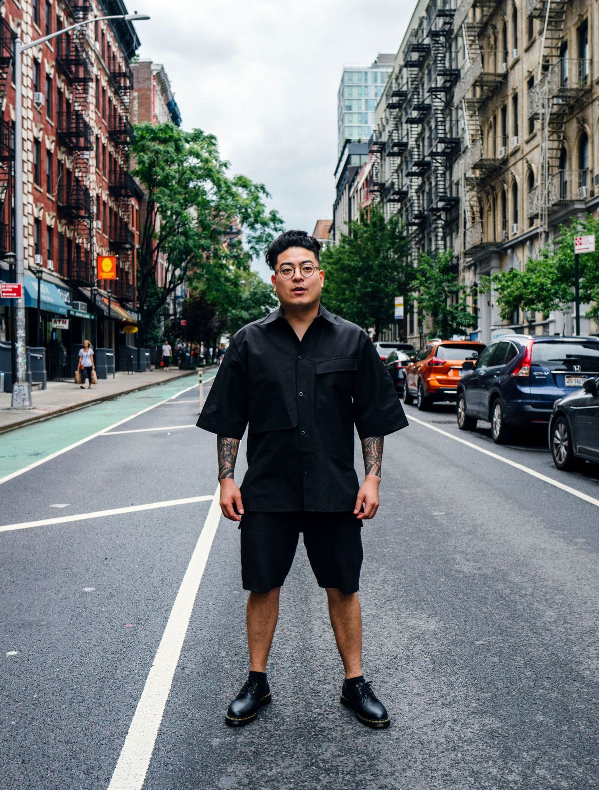 Jae Lee standing in black shorts in the middle of the street in the East Village