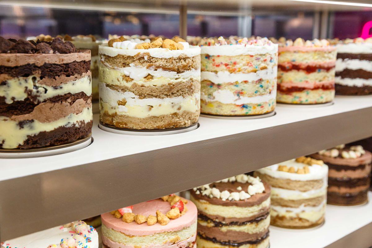 Two shelves are lined with exposed cakes form Milk Bar.