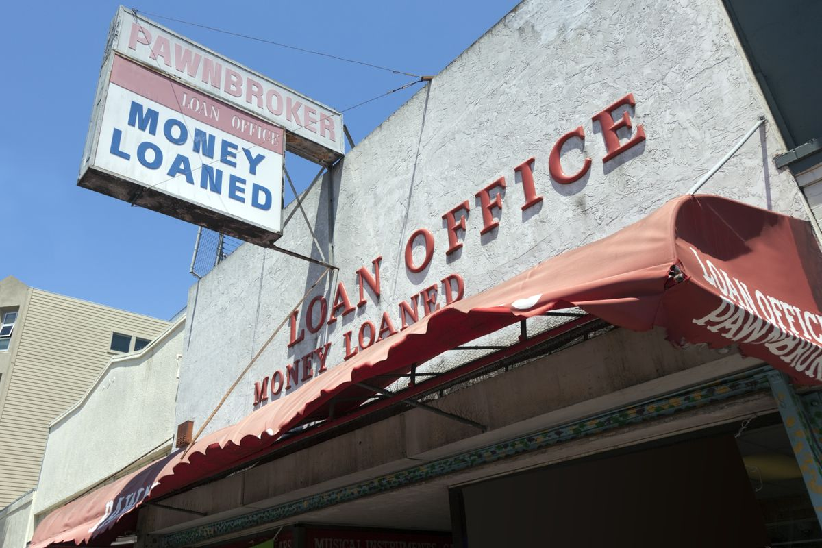 """A building exterior with signs reading """"loan office,"""" """"money loaned,"""" and """"pawnbroker."""""""