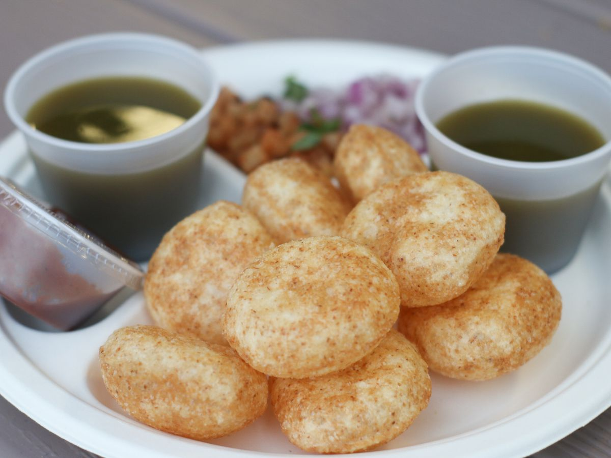 A plate of pani puri, with the tubs of green pani (spicy-sweet water) on the side
