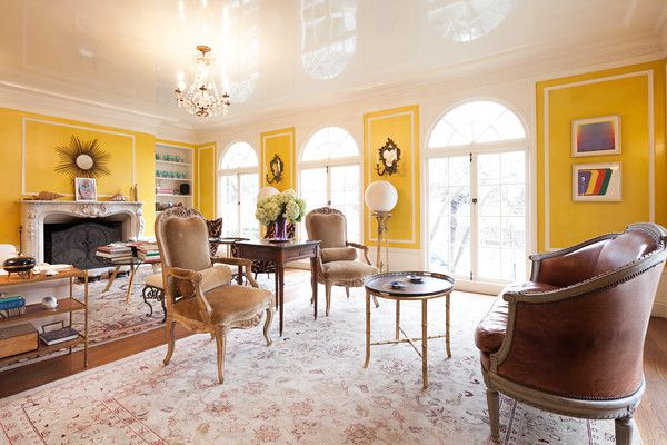 A living area with chairs, a table, a fireplace, and a couch. The walls are bright yellow. There is a chandelier hanging from the ceiling.