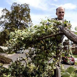Michel VanDam helps clean up his neighbor's yard in Bountiful on Wednesday, Sept. 9, 2020. Tuesday's windstorm reached over 100 mph in certain areas and caused significant property damage.