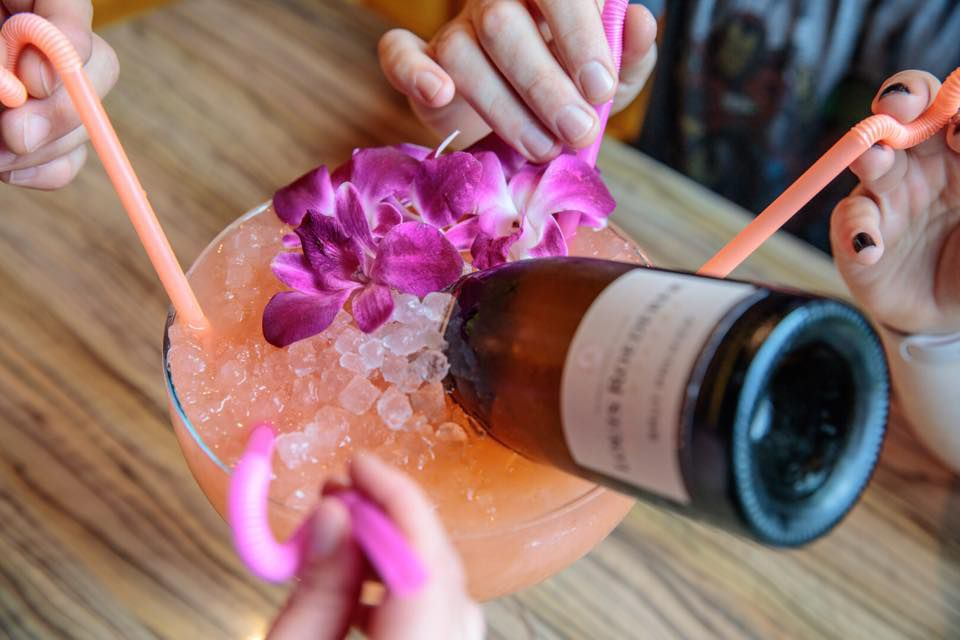 Four hands grab pink straws leading to a big glass of a shared pink cocktail, garnished with orchids. A bottle of champagne is tipped into the glass.
