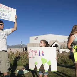 Dylan Hincks, 7, center, holds a sign along with Natasha Hincks, right, and Josh Henderson during a rally asking Utah Gov. Gary Herbert to shut down Stericycle's medical waste incinerator in North Salt Lake on Thursday, Sept. 25, 2014.