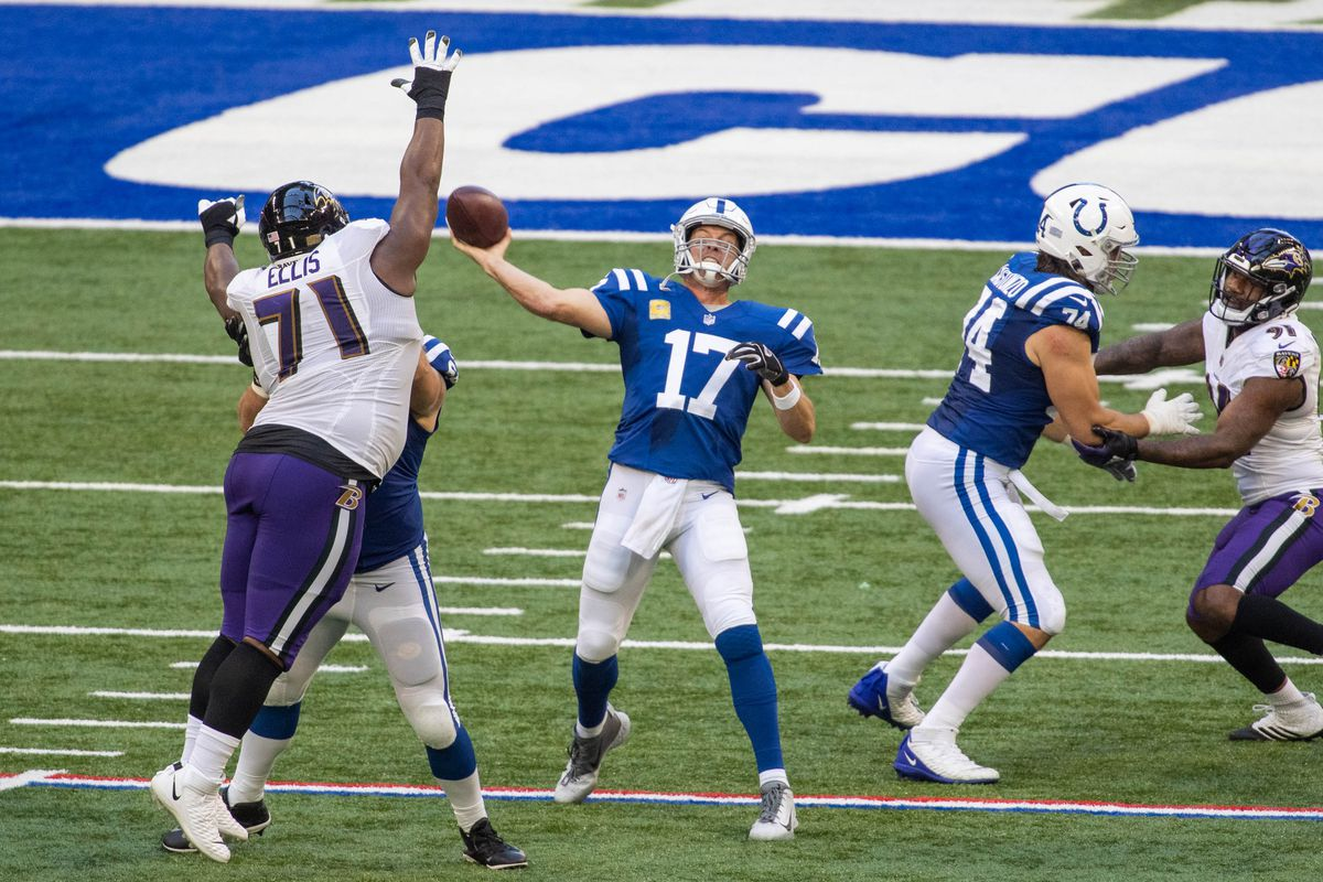 Indianapolis Colts quarterback Philip Rivers passes the ball over Baltimore Ravens defensive tackle Justin Ellis  in the second half at Lucas Oil Stadium