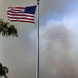 A flag an an elementary school flies horizontal as seen in view of smoke billowing from a wildfire near Monday, Sept. 10, 2012, in Wenatchee, Wash. Crews in central Washington and Wyoming worked Monday to protect homes from two of the many wildfires burning throughout the West as a destructive fire season stretches into September with no relief expected from the weather anytime soon. The National Weather service issued red-flag warnings for wide swaths of eastern Washington and Oregon, Idaho, Montana and all of Wyoming, meaning conditions could exacerbate blazes.