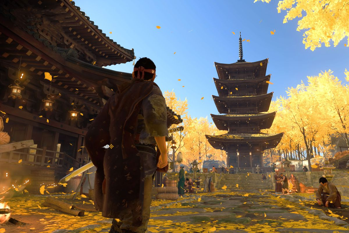 Ghost of Tsushima's main character standing in a temple with yellow leaves