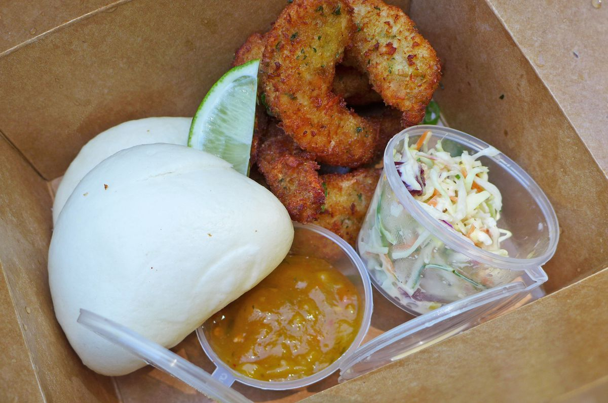 A brown box with steamed buns, slaw, sauce, and pile of fried shrimp.