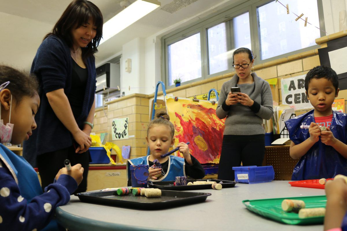 Yvette Ho, right, taps out a request to NYCHA to fix a leaky roof at CPC Jacob Riis Child Care Center. Meanwhile, a student shows her art project to Mary Cheng, who oversees early childhood programs for the Chinese-American Planning Council, a nonprofit that runs the daycare.
