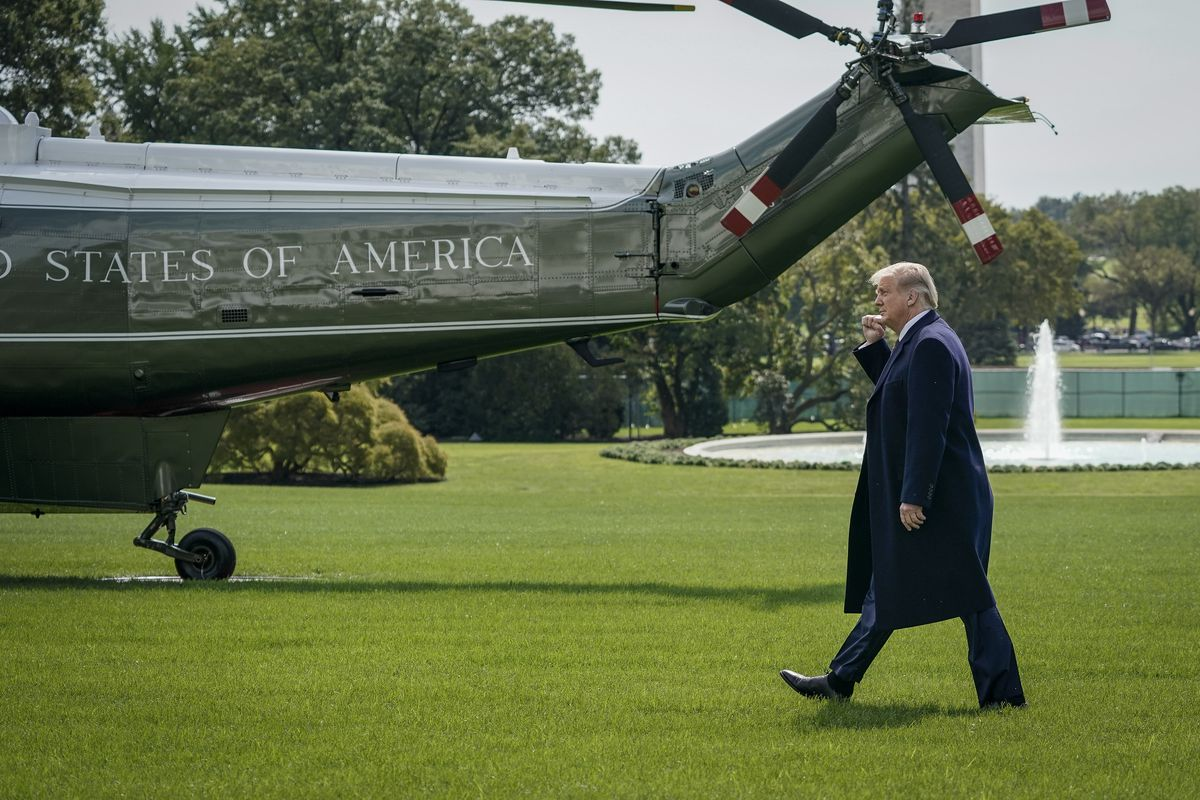 Trump walking toward a helicopter and saluting.