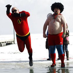 """Josh Hensley, """"Mr. Incredible,"""" and Jimmy Clayton, """"Nacho Libre,"""" begin their plunge into the frigid waters of Utah Lake Saturday for the Polar Plunge in Saratoga Springs to raise money for Special Olympics Utah."""