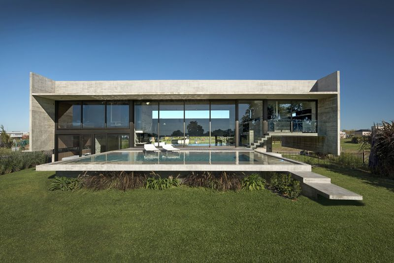 Back view of concrete house featuring infinity pool.