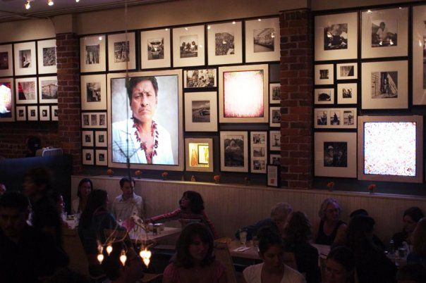 An interior wall at La Carta de Oaxaca and a handful of diners sitting at tables.