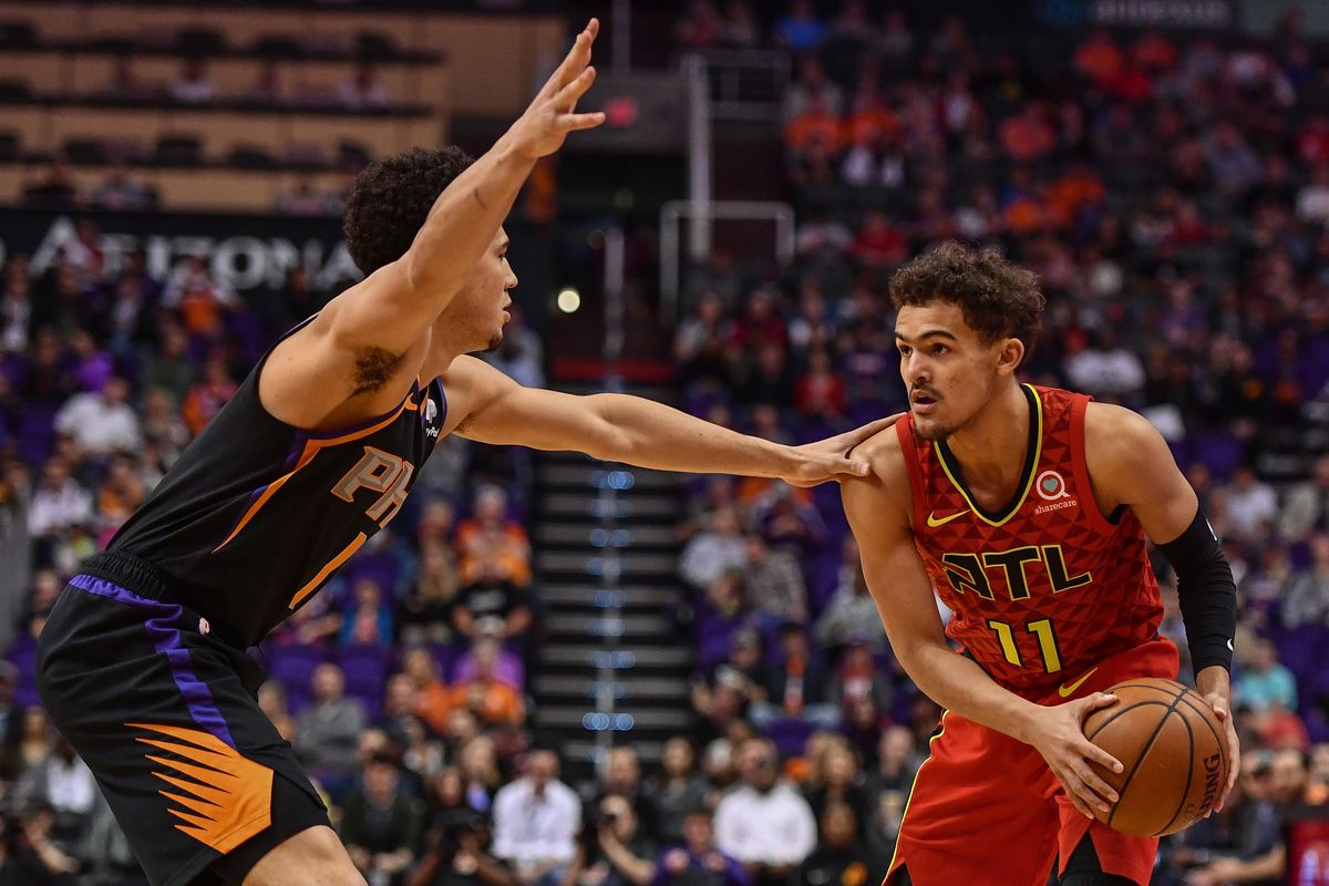 Atlanta Hawks guard Trae Young handles the ball against Phoenix Suns guard Devin Booker in the first half at Talking Stick Resort Arena.
