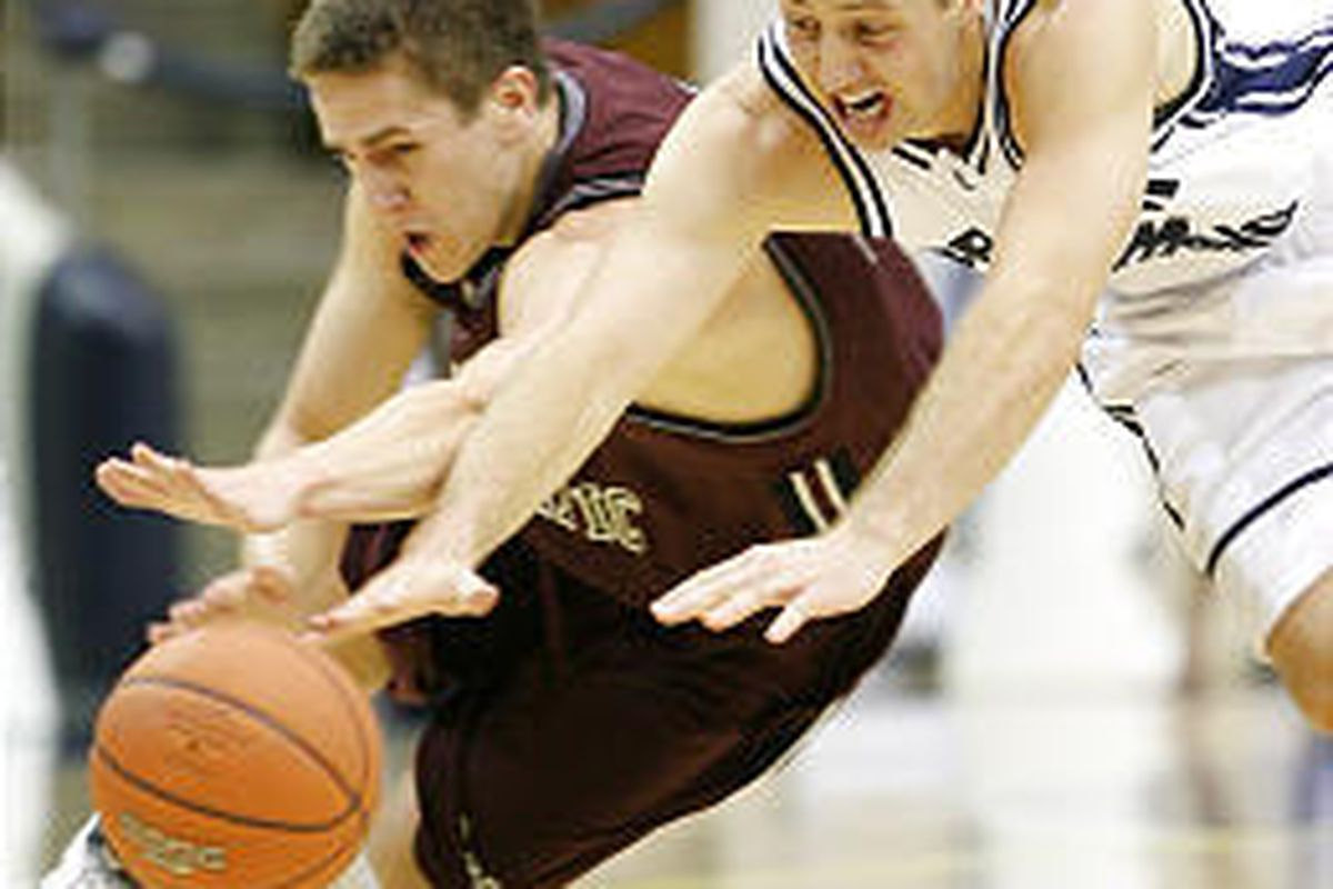 Seattle Pacific's Dustin Bremerman, left, and BYU's Austin Ainge dive for a loose ball during the first half.