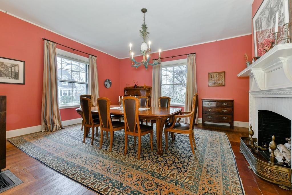 A dining room with a large table with chairs and a fireplace.