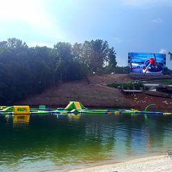 """This floating attraction, dubbed """"Aquatic Adventure,"""" is currently the park's most popular attraction, bringing kids through an inflatable obstacle course. Behind it, a massive TV plays popular music videos."""