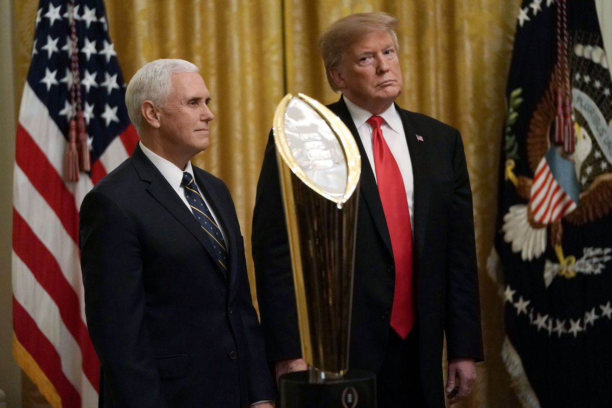 President Donald Trump stands alongside Vice President Mike Pence at an event to honor the Clemson Tigers football team at the White House in January 2019.