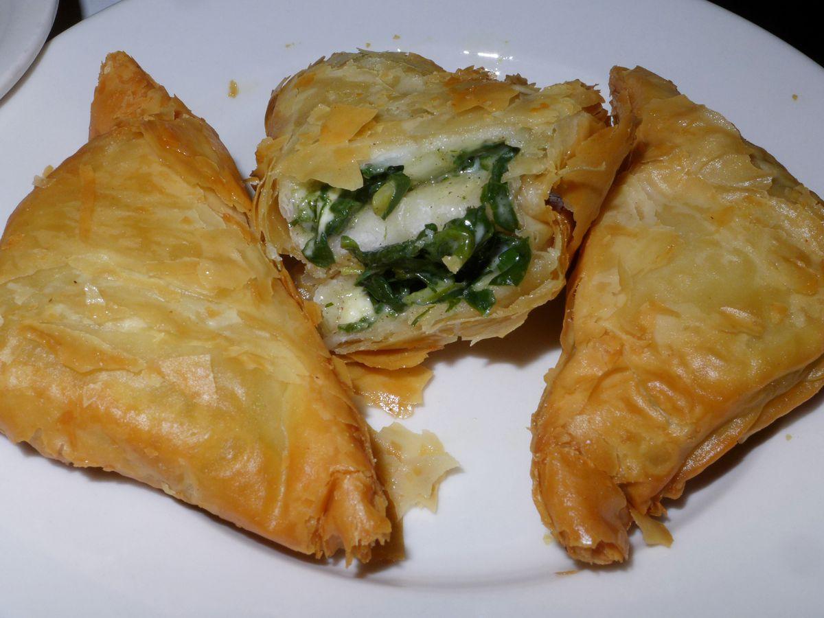Three triangular spinach pies.