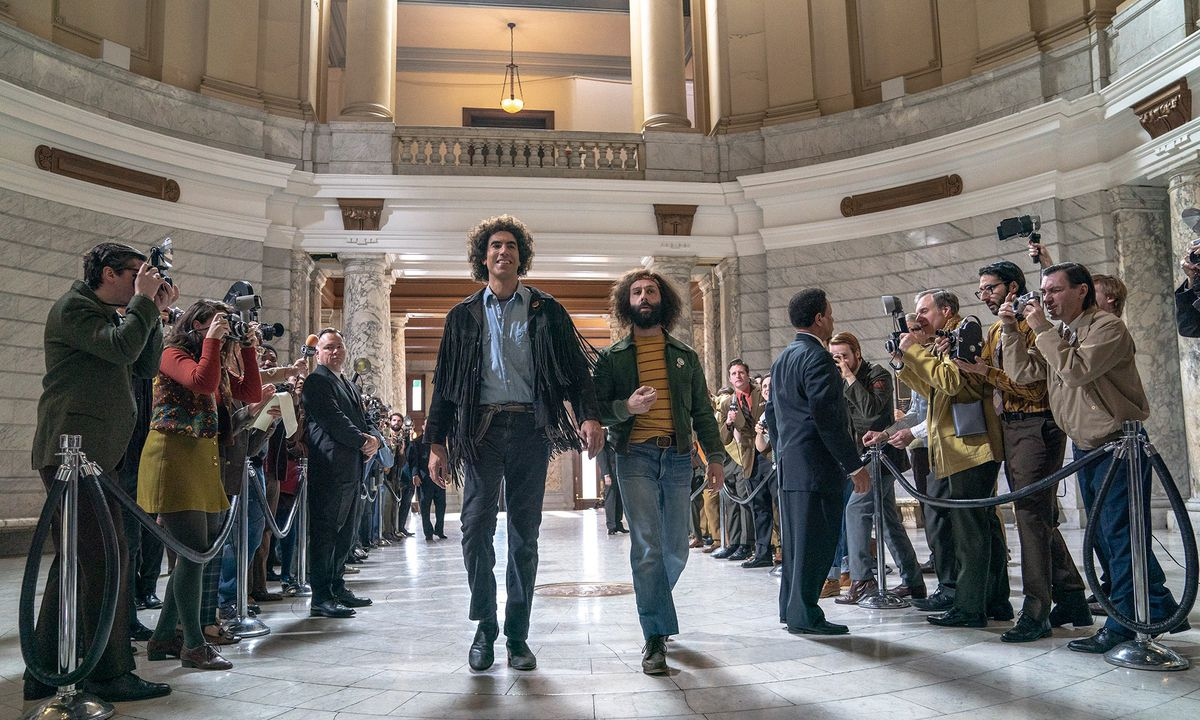 Two men in hippie garb stride through a courtroom rotunda.