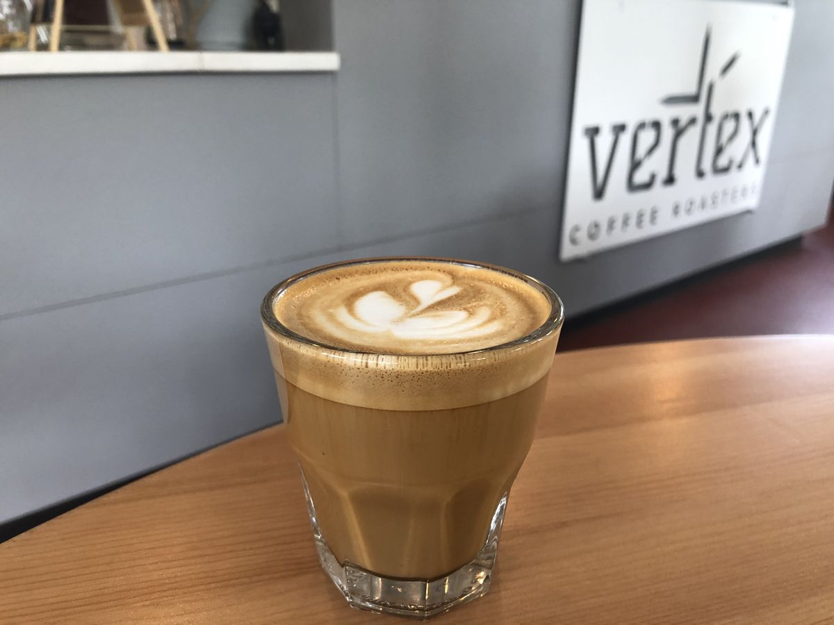 A latte in an espresso-style glass tumbler sits on a table in front of a gray wall with a sign for Vertex.