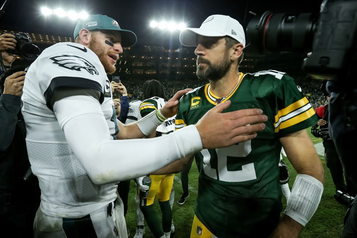 Carson Wentz #11 of the Philadelphia Eagles and Aaron Rodgers #12 of the Green Bay Packers meet after the Eagles beat the Packers 34-27 at Lambeau Field on September 26, 2019 in Green Bay, Wisconsin.