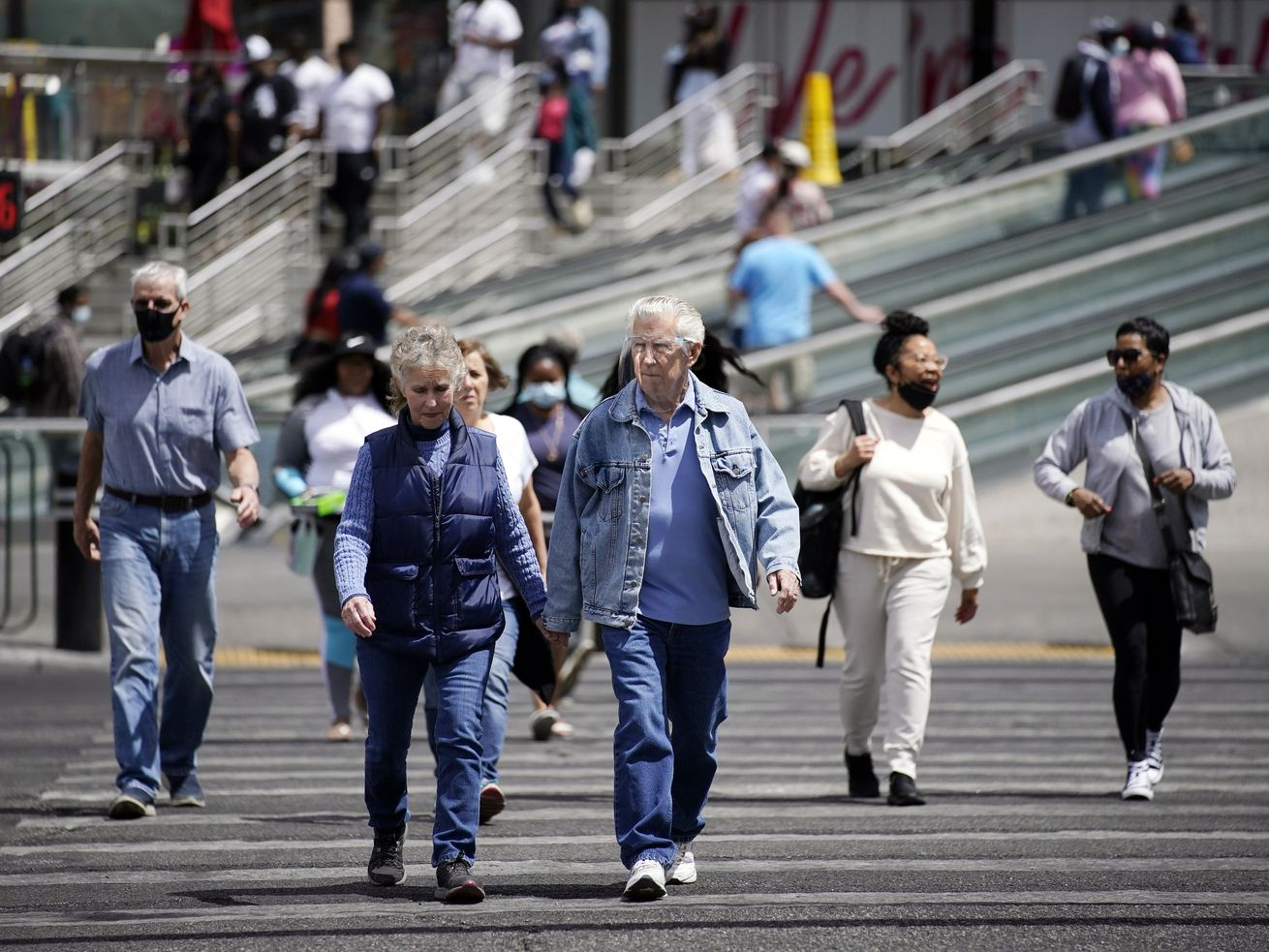 Masked and unmasked pedestrians walk across Las Vegas Boulevard, Tuesday, April 27, 2021, in Las Vegas. The Centers for Disease Control and Prevention eased its guidelines Tuesday on the wearing of masks outdoors, saying fully vaccinated Americans don't need to cover their faces anymore unless they are in a big crowd of strangers.