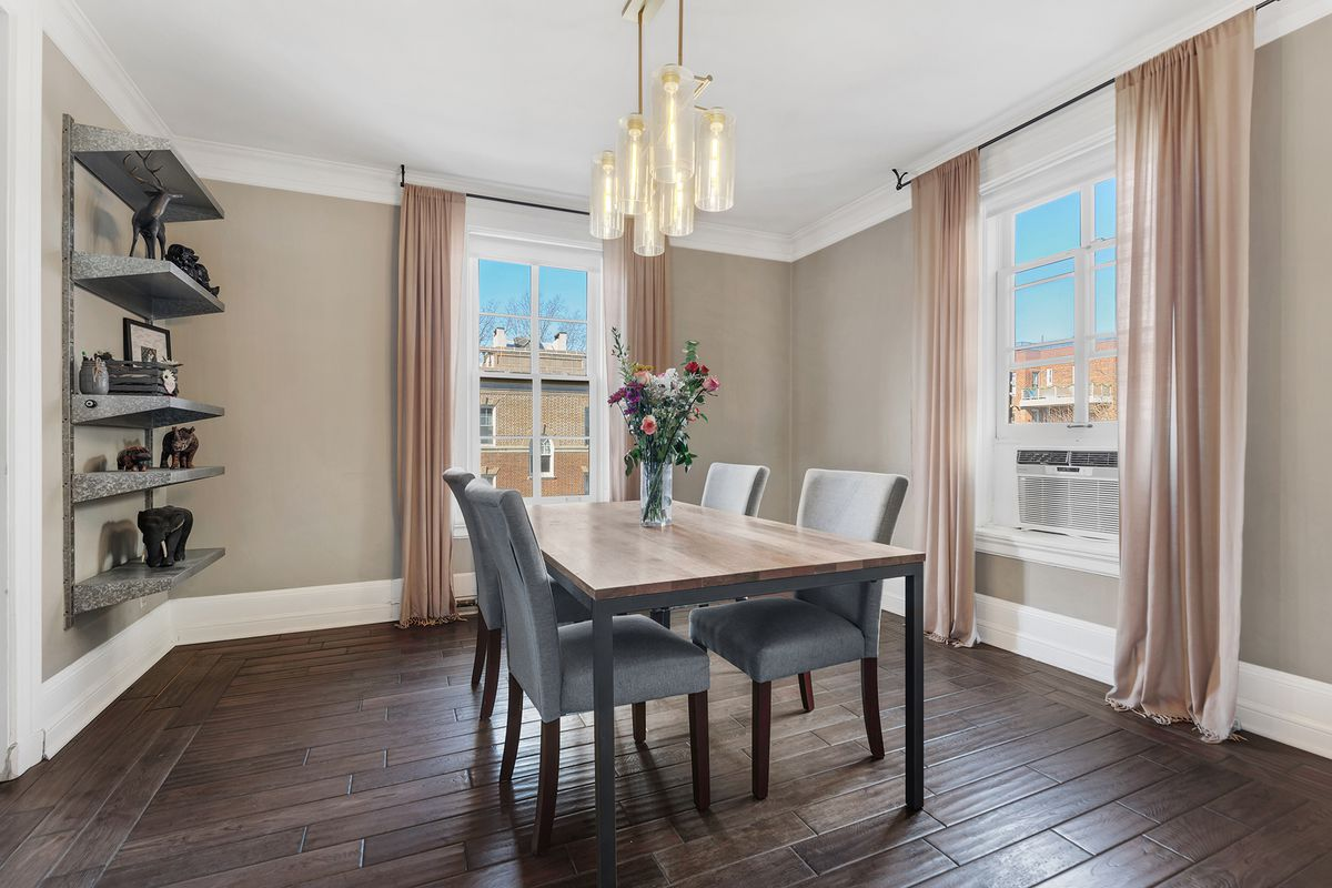 A dining area with hardwood floors, two windows, pink curtains, and a rectangular dining table.