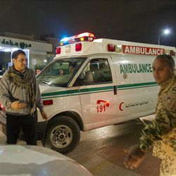 In this photo taken on a government organized tour, Libyan soldier and a civilian attempt to conduct traffic following an airstrike in Tripoli, Libya, early Tuesday, May 10, 2011. (AP Photo/Darko Bandic)
